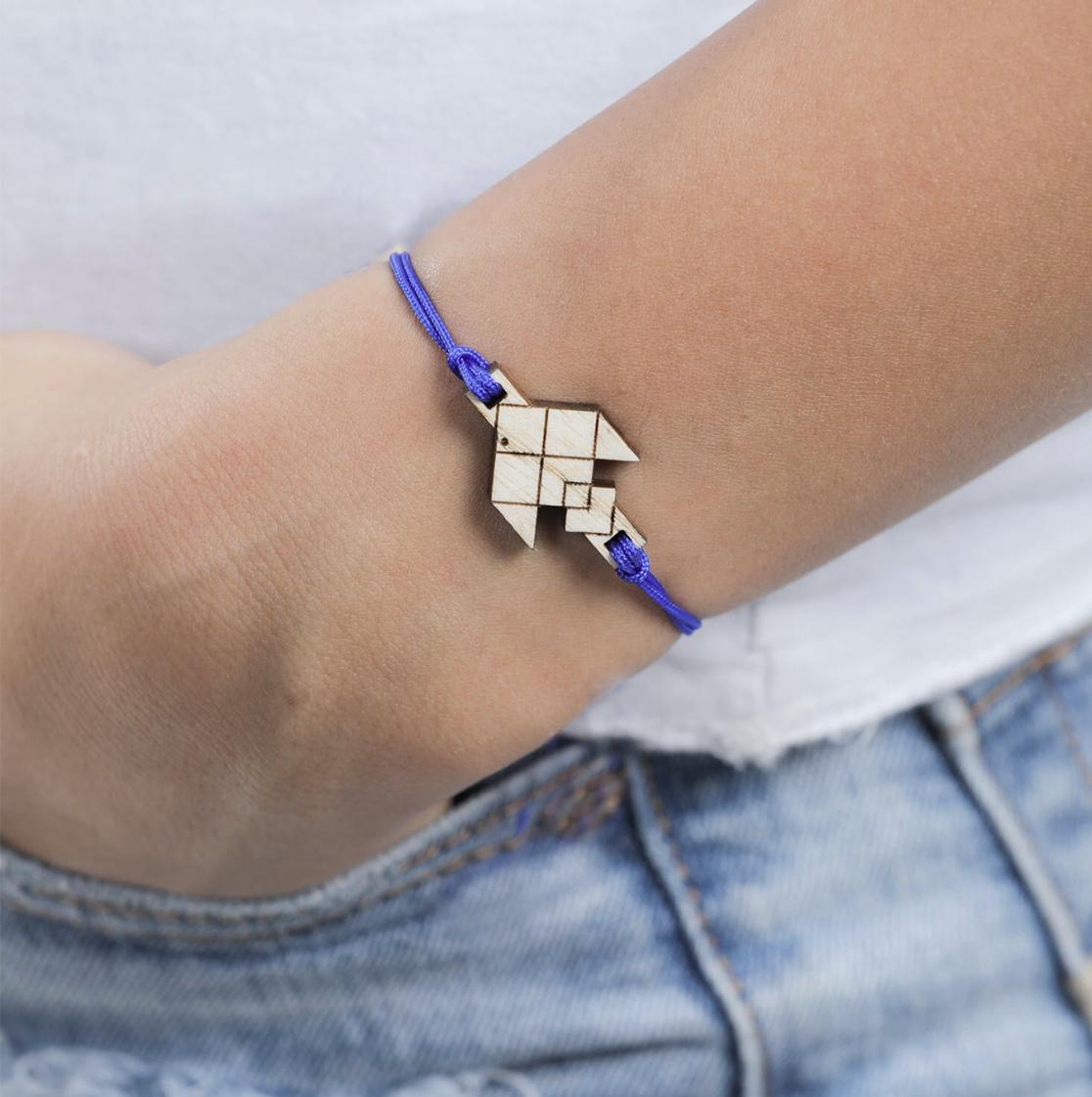 main qui porte un bracelet cordon bleu avec pendentif en bois en forme de poisson volant