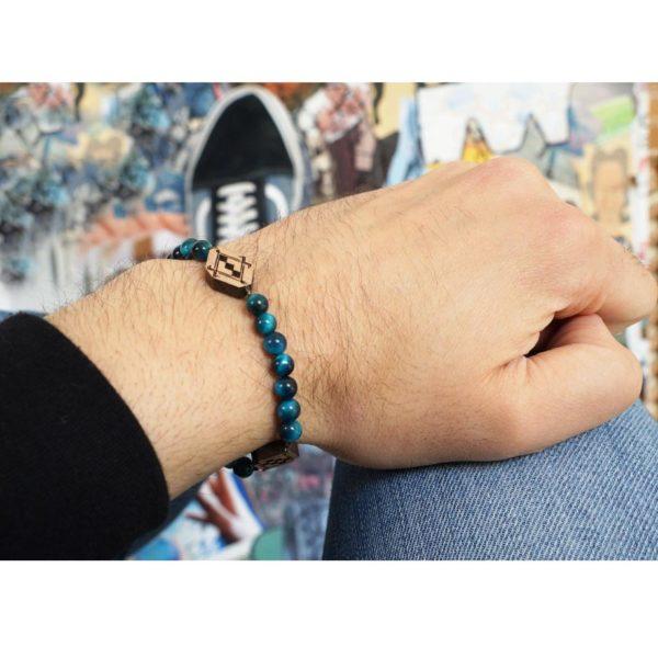 main portant un bracelet avec perles bleus et pendentifs en bois