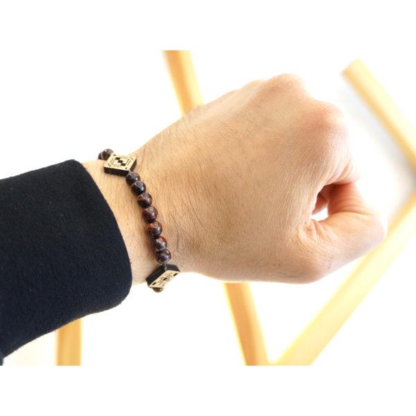 main portant un bracelet avec perles et pendentif en bois