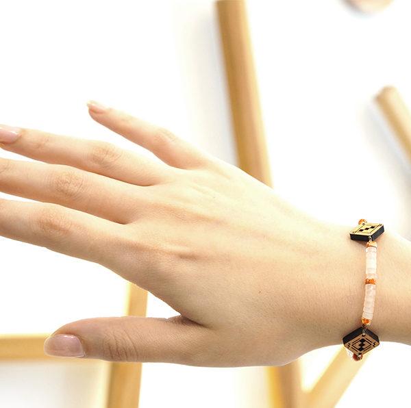 Main qui porte un bracelet blanc en bois