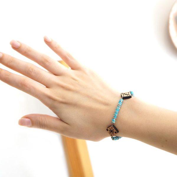 main qui porte un bracelet berbère en bois et en pierre naturelle