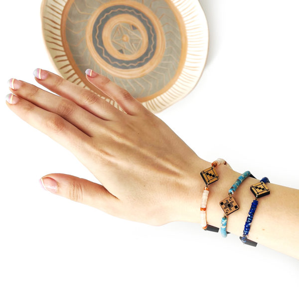 main qui porte 3 bracelets berbères en bois et en pierre naturelles